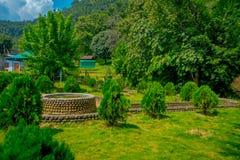 POKHARA NEPAL OKTOBER 10, 2017: Härlig trädgård i skriva in av slagträgrottan med en asfull struktur i mitt av Arkivbild
