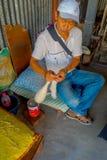 POKHARA NEPAL - OKTOBER 06 2017: Inomhus sikt av oidentifierat mansammanträde i en stol och en snurr ullen inom av a Royaltyfri Fotografi