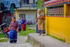 POKHARA, NEPAL - OKTOBER 06 2017: Niet geïdentificeerde vrouwenpilgrin die dicht bij een het bidden wiel in Tibetaanse Tempel, Pa stock afbeelding