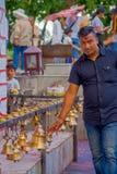 POKHARA NEPAL OKTOBER 10, 2017: Oidentifierad affärsman som bär en svart t-skjorta och trycker på klockorna av olikt Arkivbild