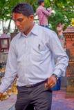POKHARA NEPAL OKTOBER 10, 2017: Oidentifierad affärsman som trycker på klockorna av det olika formatet som hänger i Taal Barahi Royaltyfria Foton