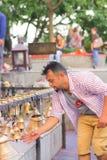 POKHARA NEPAL OKTOBER 10, 2017: Oidentifierad affärsman som trycker på klockorna av det olika formatet som hänger i Taal Barahi Royaltyfri Foto