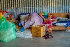 POKHARA NEPAL - OKTOBER 06 2017: Oidentifierad gammal kvinna som sover efter ett hårt hö som arbetar på fabriks- ull för vävstol Royaltyfri Bild