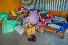 POKHARA NEPAL - OKTOBER 06 2017: Oidentifierad gammal kvinna som sover efter ett hårt hö som arbetar på fabriks- ull för vävstol Arkivbilder