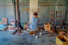POKHARA NEPAL - OKTOBER 06 2017: Oidentifierad kvinna som arbetar på för ullsjal för vävstol fabriks- kläder i Nepal Arkivfoton