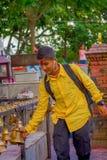 POKHARA NEPAL OKTOBER 10, 2017: Oidentifierad man som bär en gul t-skjorta som trycker på klockorna av olikt hänga för format Royaltyfri Fotografi