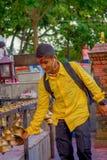 POKHARA NEPAL OKTOBER 10, 2017: Oidentifierad man som bär en gul t-skjorta som trycker på klockorna av olikt hänga för format Royaltyfri Bild