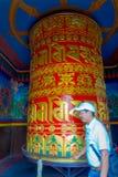 POKHARA NEPAL - OKTOBER 06 2017: Oidentifierad man som nästan går abstrakt, av ett mycket stort buddistiskt bönhjul Arkivfoton