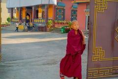 POKHARA NEPAL - OKTOBER 06 2017: Oidentifierad pojke för buddistisk munk som nästan går en dörr på den Tashi flyktingbosättningen Royaltyfri Foto