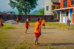 POKHARA NEPAL - OKTOBER 06 2017: Oidentifierad tonåring för buddistisk munk som spelar fotboll på den Sakya Tangyud kloster in Royaltyfri Bild
