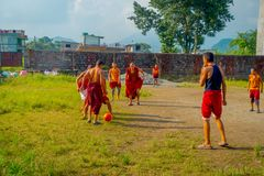 POKHARA NEPAL - OKTOBER 06 2017: Oidentifierad tonåring för buddistisk munk som spelar fotboll på den Sakya Tangyud kloster in Royaltyfria Foton