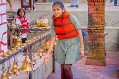 POKHARA NEPAL OKTOBER 10, 2017: Oidentifierad ung kvinna som trycker på klockorna av det olika formatet som hänger i Taal Barahi Royaltyfri Foto