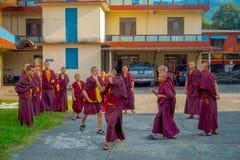 POKHARA NEPAL - OKTOBER 06 2017: Oidentifierade tonåringar för buddistisk munk som tycker om den fria tiden i en uteplats och spe Royaltyfria Foton