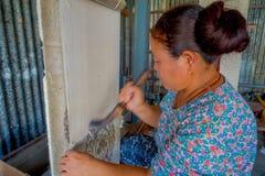 POKHARA NEPAL - OKTOBER 06 2017: Stäng sig upp av den oidentifierade kvinnan som in arbetar på för ullsjal för vävstol fabriks- k Royaltyfria Foton