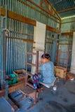 POKHARA NEPAL - OKTOBER 06 2017: Stäng sig upp av den oidentifierade kvinnan som in arbetar på för ullsjal för vävstol fabriks- k Royaltyfri Foto