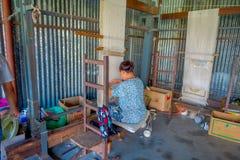 POKHARA NEPAL - OKTOBER 06 2017: Stäng sig upp av den oidentifierade kvinnan som in arbetar på för ullsjal för vävstol fabriks- k Royaltyfri Fotografi
