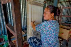 POKHARA NEPAL - OKTOBER 06 2017: Stäng sig upp av den oidentifierade le kvinnan som arbetar på den fabriks- ullsjalen för vävstol Royaltyfri Fotografi