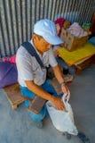 POKHARA NEPAL - OKTOBER 06 2017: Stäng sig upp av oidentifierat mansammanträde i en stol och besparing inom av en plastpåse Royaltyfri Bild