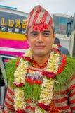 POKHARA NEPAL OKTOBER 10, 2017: Stående av bärande blommor för en stilig man runt om hans hals och bärande typisk kläder Arkivfoto