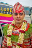 POKHARA NEPAL OKTOBER 10, 2017: Stående av bärande blommor för en stilig man runt om hans hals och bärande typisk kläder Fotografering för Bildbyråer