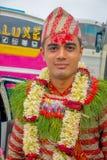 POKHARA NEPAL OKTOBER 10, 2017: Stående av bärande blommor för en stilig man runt om hans hals och bärande typisk kläder Royaltyfri Bild