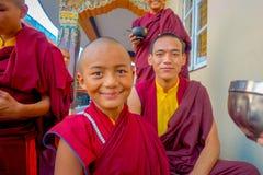 POKHARA NEPAL - OKTOBER 06 2017: Stående av den oidentifierade tonåringen för buddistisk munk som tycker om den fria tiden med de Arkivbild