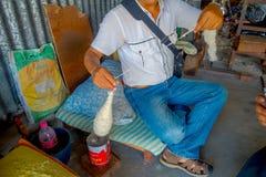 POKHARA, NEPAL - 6 OTTOBRE 2017: Chiuda su dell'uomo non identificato che si siede in una sedia e che fila la lana dentro della a Immagine Stock