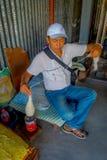 POKHARA, NEPAL - 6 OTTOBRE 2017: Chiuda su dell'uomo non identificato che si siede in una sedia e che fila la lana dentro della a Fotografia Stock Libera da Diritti