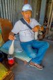 POKHARA, NEPAL - 6 OTTOBRE 2017: Chiuda su dell'uomo non identificato che si siede in una sedia e che fila la lana dentro della a Fotografie Stock