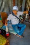 POKHARA, NEPAL - 6 OTTOBRE 2017: Chiuda su dell'uomo non identificato che si siede in una sedia e che fila la lana dentro della a Fotografia Stock