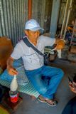 POKHARA, NEPAL - 6 OTTOBRE 2017: Chiuda su dell'uomo non identificato del hardworker che si siede in una sedia e che fila la lana Immagine Stock