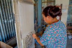 POKHARA, NEPAL - 6 OTTOBRE 2017: Chiuda su della donna non identificata che lavora all'abbigliamento dello scialle della lana di  Fotografia Stock