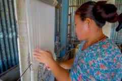 POKHARA, NEPAL - 6 OTTOBRE 2017: Chiuda su della donna non identificata che lavora all'abbigliamento dello scialle della lana di  Fotografia Stock Libera da Diritti