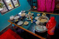 POKHARA NEPAL, PAŹDZIERNIK, - 06 2017: Asortowany Nepalski śniadanie słuzyć na stole, mleko, słoju coffe, naczynie, talerze insid Zdjęcie Stock