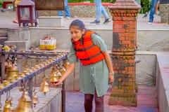 POKHARA, NEPAL PAŹDZIERNIK 10, 2017: Niezidentyfikowana młoda kobieta dotyka dzwony różny wielkościowy obwieszenie w Taal Barahi Zdjęcie Stock