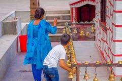 POKHARA, NEPAL PAŹDZIERNIK 10, 2017: Niezidentyfikowani ludzie dotyka dzwony różny wielkościowy obwieszenie w Taal Barahi Mandir Obrazy Royalty Free