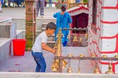 POKHARA, NEPAL PAŹDZIERNIK 10, 2017: Niezidentyfikowani ludzie dotyka dzwony różny wielkościowy obwieszenie w Taal Barahi Mandir Obrazy Stock