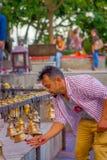 POKHARA, NEPAL PAŹDZIERNIK 10, 2017: Niezidentyfikowany biznesmen dotyka dzwony różny wielkościowy obwieszenie w Taal Barahi Obraz Stock