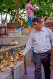POKHARA, NEPAL PAŹDZIERNIK 10, 2017: Niezidentyfikowany biznesmen dotyka dzwony różny wielkościowy obwieszenie w Taal Barahi Zdjęcia Stock