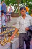 POKHARA, NEPAL PAŹDZIERNIK 10, 2017: Niezidentyfikowany biznesmen dotyka dzwony różny wielkościowy obwieszenie w Taal Barahi Zdjęcia Royalty Free