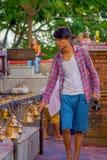 POKHARA, NEPAL PAŹDZIERNIK 10, 2017: Niezidentyfikowany młody człowiek dotyka dzwony różny wielkościowy obwieszenie w Taal Barahi Zdjęcie Stock