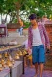 POKHARA, NEPAL PAŹDZIERNIK 10, 2017: Niezidentyfikowany młody człowiek dotyka dzwony różny wielkościowy obwieszenie w Taal Barahi Zdjęcia Stock
