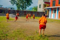 POKHARA NEPAL, PAŹDZIERNIK, - 06 2017: Niezidentyfikowany mnicha buddyjskiego nastolatek bawić się piłkę nożną przy Sakya Tangyud Zdjęcie Royalty Free