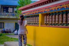 POKHARA NEPAL, PAŹDZIERNIK, - 06 2017: Niezidentyfikowany pilgrin dotyka modlenie toczy wewnątrz Tybetańską świątynię, Padum, Kas Fotografia Stock