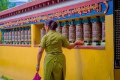 POKHARA NEPAL, PAŹDZIERNIK, - 06 2017: Niezidentyfikowany pilgrin dotyka modlenie toczy wewnątrz Tybetańską świątynię, Padum, Kas Zdjęcia Royalty Free