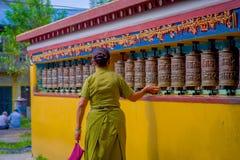 POKHARA NEPAL, PAŹDZIERNIK, - 06 2017: Niezidentyfikowany pilgrin dotyka modlenie toczy wewnątrz Tybetańską świątynię, Padum, Kas Zdjęcie Stock