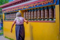 POKHARA NEPAL, PAŹDZIERNIK, - 06 2017: Niezidentyfikowany starej kobiety pilgrin dotyka modlenie toczy wewnątrz Tybetańską świąty Obraz Royalty Free