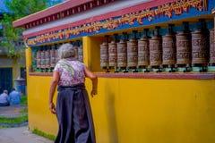POKHARA NEPAL, PAŹDZIERNIK, - 06 2017: Niezidentyfikowany starej kobiety pilgrin dotyka modlenie toczy wewnątrz Tybetańską świąty Fotografia Royalty Free