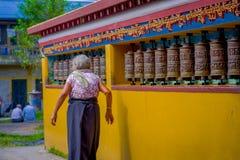 POKHARA NEPAL, PAŹDZIERNIK, - 06 2017: Niezidentyfikowany starej kobiety pilgrin dotyka modlenie toczy wewnątrz Tybetańską świąty Obrazy Royalty Free