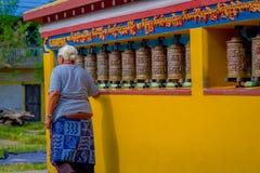 POKHARA NEPAL, PAŹDZIERNIK, - 06 2017: Niezidentyfikowany starej kobiety pilgrin dotyka modlenie toczy wewnątrz Tybetańską świąty Zdjęcia Royalty Free
